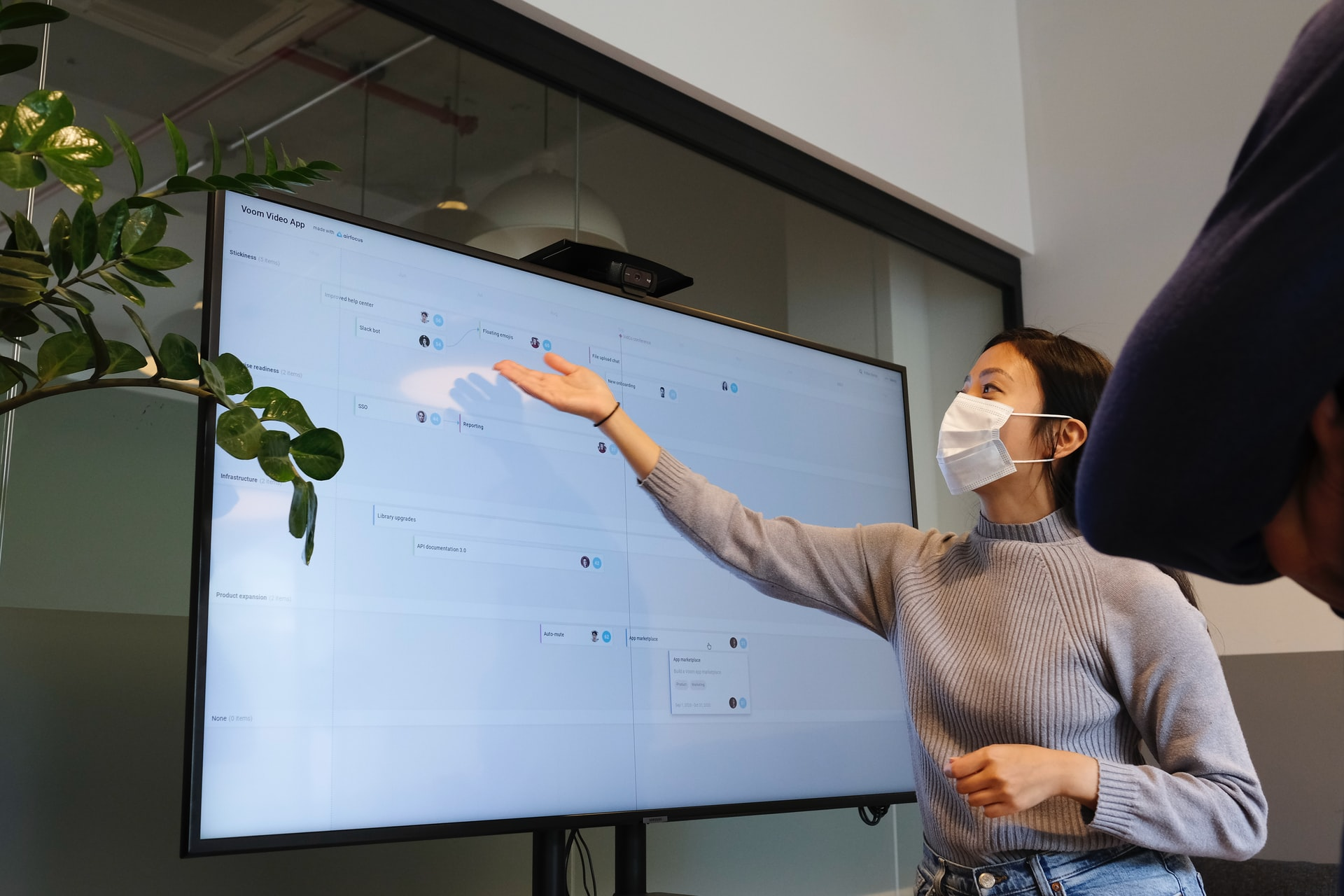 Woman wearing face mask presenting at large screen